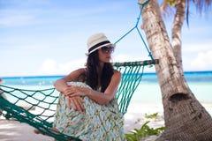 Mujer en el sombrero que se sienta en hamaca en la sombra del árbol Imagenes de archivo