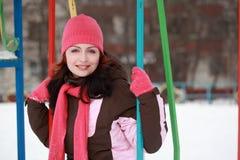 Mujer en el sombrero rosado que se sienta en el oscilación en invierno Imagen de archivo libre de regalías