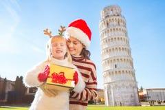 Mujer en el sombrero y el bebé de la Navidad que sostienen la caja de regalo pisa Imágenes de archivo libres de regalías