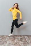 Mujer en el suéter amarillo que salta y que habla en el teléfono móvil Fotografía de archivo libre de regalías