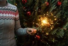Mujer en el suéter hecho punto que sostiene bengalas antes de árbol de navidad imágenes de archivo libres de regalías