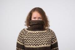 Mujer en el suéter marrón caliente que oculta su cara Solamente se ven los ojos Ella quiere permanecer el anónimo fotos de archivo