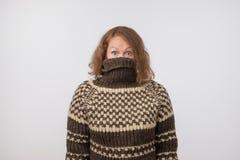 Mujer en el suéter marrón caliente que oculta su cara Solamente se ven los ojos Ella quiere permanecer el anónimo foto de archivo libre de regalías
