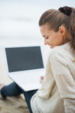Mujer en el suéter que se sienta en la playa sola y que usa el ordenador portátil Imágenes de archivo libres de regalías