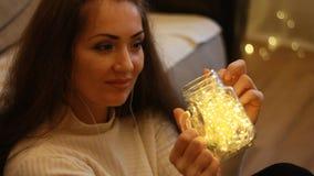 Mujer en el sueño de los auriculares Fondo con las luces del bokeh almacen de video