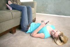 Mujer en el suelo texting en el teléfono celular Imagenes de archivo