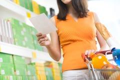 Mujer en el supermercado con la lista de compras Fotografía de archivo libre de regalías