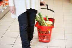 Mujer en el supermercado que tira de la cesta fotos de archivo