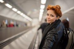 Mujer en el túnel de la escalera móvil del metro Imagenes de archivo
