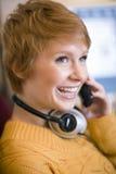 Mujer en el teléfono celular con los auriculares Fotos de archivo libres de regalías