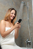 Mujer en el teléfono en la ducha mientras que es aguas el residual Imágenes de archivo libres de regalías