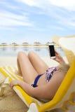 Mujer en el teléfono móvil en vacaciones tropicales de la playa fotografía de archivo