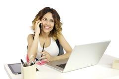 Mujer en el teléfono mientras que trabaja con el ordenador Imagenes de archivo
