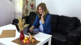 Mujer en el teléfono mientras que trabaja en el ordenador portátil en hogar cómodo almacen de metraje de vídeo