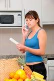 Mujer en el teléfono que controla la cuenta Foto de archivo libre de regalías