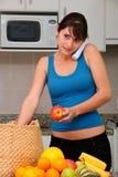 Mujer en el teléfono que desempaqueta las tiendas de comestibles Foto de archivo libre de regalías