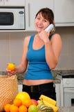 Mujer en el teléfono que desempaqueta las tiendas de comestibles Imagenes de archivo