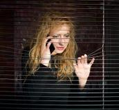 Mujer en el teléfono que mira a través de las persianas imagenes de archivo