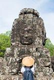 Mujer en el templo de Bayon que mira las caras de piedra, Angkor Thom, cielo azul claro de la luz de la ma?ana Concepto de la med imagen de archivo