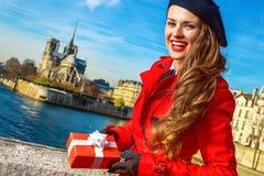 Mujer en el terraplén en París que muestra la caja del regalo de Navidad fotos de archivo libres de regalías