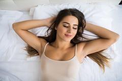 mujer en el top que miente en cama con las manos bajo cabeza fotos de archivo libres de regalías