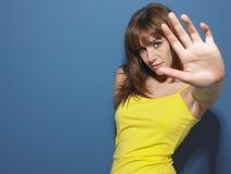 Mujer en el top sin mangas amarillo que gesticula la muestra de la parada Imagen de archivo libre de regalías