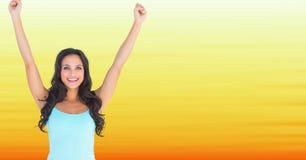 Mujer en el top sin mangas que celebra contra fondo amarillo borroso Imagenes de archivo