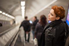 Mujer en el tounel de la escalera móvil del metro Fotos de archivo libres de regalías