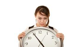 Mujer en el trabajo que celebra el reloj grande Foto de archivo