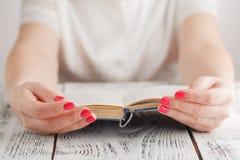 Mujer en el trabajo que se aferra a un libro que mueve de un tirón a través de las páginas Imagen de archivo
