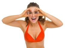 Mujer en el traje de baño que mira a través de los prismáticos Imagen de archivo libre de regalías