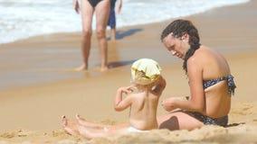 Mujer en el traje de baño que se sienta en la playa arenosa con la pequeña hija y hablar almacen de video