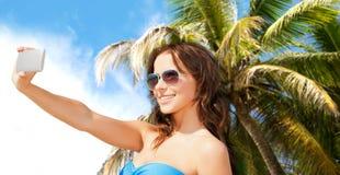 Mujer en el traje de baño que toma el selfie con smatphone Imagen de archivo libre de regalías