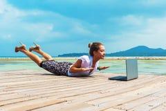 Mujer en el traje de la oficina que hace yoga con el ordenador portátil Imagen de archivo