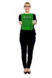 Mujer en el traje de negocios que visualiza la calculadora verde grande imagen de archivo libre de regalías