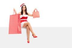 Mujer en el traje de Papá Noel que sostiene los panieres Imagen de archivo