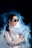 Mujer en el traje de plata del espacio que sostiene el arma de la pistola Foto de archivo libre de regalías