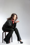 Mujer en el traje negro que se sienta en un taburete Fotografía de archivo libre de regalías