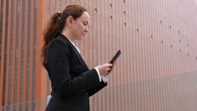 Mujer en el traje que manda un SMS en smartphone en el centro de la ciudad de la ciudad almacen de video
