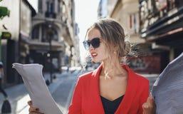 Mujer en el traje rojo que mira escéptico los documentos Imagen de archivo