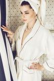 Mujer en el traje y la toalla que miran hacia fuera la ventana Fotos de archivo libres de regalías