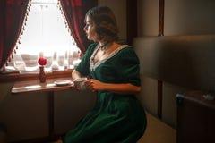 Mujer en el tren del vintage, interior rico del compartimiento Foto de archivo