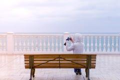Mujer en el vídeo blanco de las ondas del mar de los lanzamientos de la chaqueta y de la capilla en el smartphone que se sienta e fotografía de archivo