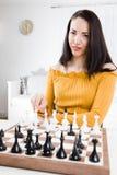 Mujer en el vestido amarillo que se sienta delante del ajedrez - planeamiento foto de archivo