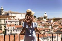 Mujer en el vestido azul, lookimg del sombrero del sol en la opinión im Lisboa Alfama, Portugal del panorama Imagen de archivo libre de regalías