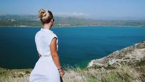 Mujer en el vestido blanco del verano que admira del paisaje mediterráneo escénico superior Vuelo del vestido en el viento amazin almacen de metraje de vídeo
