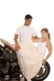 Mujer en el vestido blanco en soporte del hombre de la motocicleta detrás fotografía de archivo