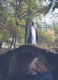 Mujer en el vestido blanco en un puente de piedra Foto de archivo