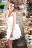 Mujer en el vestido blanco en la playa tropical cerca de las palmeras Fotos de archivo