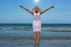Mujer en el vestido blanco que aumenta los brazos que miran el océano Imagenes de archivo